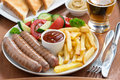 Lunch With Grilled Sausages, French Fries, Vegetables And Beer Royalty Free Stock Photography - 44900957