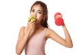Asian Healthy Girl Workout With Dumbbell Eat Apple Stock Photo - 45030440