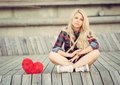 Sad Lonely Girl Sitting On Wood Planks Near To A Big Red Heart Royalty Free Stock Photo - 45043765