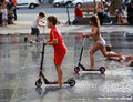Kids Rides On Scooters Among Fountains Royalty Free Stock Photos - 45074958