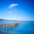Wooden Pier Or Jetty Remains On A Blue Ocean Lake. Long Exposure Royalty Free Stock Photos - 45142898