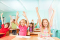 Happy Kids With Arms Up Sit In Classroom Rows Royalty Free Stock Images - 45179479