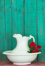 Antique Water Pitcher And Basin With Red Flowers By Rustic Green Wood Background Stock Photo - 45211750