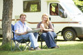 Couple Relaxing Outside Motor Home On Vacation Royalty Free Stock Photos - 45378078