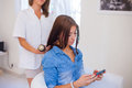 Hairdresser Combing Hair Woman With Mobile Phone In Hairdressing Stock Photo - 45412120