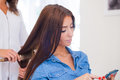 Hairdresser Doing Haircut For Women Wiht Mobile Phone In Hairdre Stock Photo - 45412140