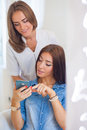 Hairdresser Combing Hair Woman With Mobile Phone In Hairdressing Stock Photos - 45412183