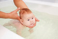 Baby Swimming In The Bath. Mother Helping Him. Stock Images - 45414844