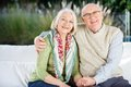 Happy Senior Man Sitting With Arm Around Woman On Stock Photography - 45599842