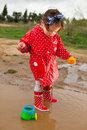 Playing With Her Water Toys On Muddly Puddles Royalty Free Stock Photography - 45623577
