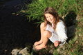 Girl Sitting By A River Stock Images - 45677224