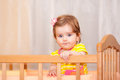 Small Child With A Hairpin Standing In Crib. Stock Photo - 45693830