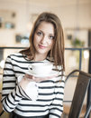 Portrait Of Young Woman Holding Coffee Cup And Saucer At Cafe Royalty Free Stock Image - 45826726