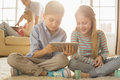 Happy Siblings Using Digital Tablet On Floor With Parents In Background Royalty Free Stock Image - 45830496