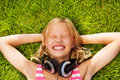 Laughing Girl With Headphones Lays On Green Grass Royalty Free Stock Photo - 45846465