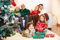 Family With Gifts At Christmas Tree Stock Photos - 45975223