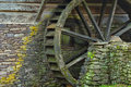 Wooden Water Paddle Wheel And Mossy Stones On The Side Of A Old Royalty Free Stock Images - 46024069