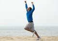 Man Running At The Beach With Arms Raised In Victory Royalty Free Stock Photo - 46055725