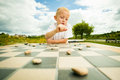 Child Playing Draughts Or Checkers Board Game Outdoor Stock Photography - 46071212