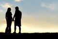 Silhouette Of Happy Couple Holding Hands And Talking At Sunset Royalty Free Stock Photography - 46173057