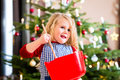 Girl Baking Cookies In Front Of Christmas Tree Stock Photography - 46179012