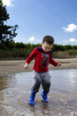 Toddler Jumping In A Puddle With His New Boots Royalty Free Stock Images - 46272829