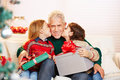 Children Kissing Grandfather With Gifts On Christmas Royalty Free Stock Photos - 46319818