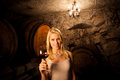 Beautiful Young Blond Woman Tasting Red Wine In A Wine Cellar Royalty Free Stock Photos - 46325618