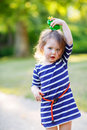 Beautiful Little Girl In Red Rain Boots Playing With Rubber Frog Royalty Free Stock Photos - 46329788