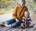 Mother And Daughter Sitting Near Lake Royalty Free Stock Image - 46336076
