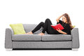 Relaxed Young Woman Reading A Book Seated On Sofa Stock Images - 46375134
