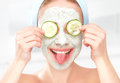 Funny Young Girl With A Mask For Skin Face And Cucumbers Stock Photography - 46506962
