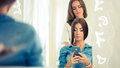 Hairdresser Doing Haircut For Women Wiht Mobile Phone In Hairdre Royalty Free Stock Images - 46566939
