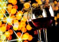 Two Red Wine Glasses Against Golden Bokeh Lights Background Royalty Free Stock Photography - 46597577