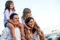 Young Couple With Kids On Shoulders Outdoors. Stock Photos - 46598423