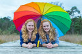 Two Girls Lying In Nature Under Colorful Umbrella Royalty Free Stock Image - 46679426