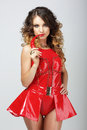 Alluring Woman In Red Rubber Outfit Biting Chili Pepper Royalty Free Stock Image - 46759366