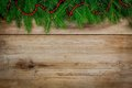Pine Tree Border With Red Garland On Old Wooden Background Royalty Free Stock Images - 46805619