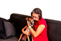 Woman Cuddling With Dog On A Grey Sofa Stock Photography - 46809022