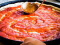 Pizza Maker Puts On The Sauce Stock Image - 46818001