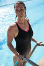 Attractive Female Swimmer On Ladder At Edge Swimming Pool Royalty Free Stock Photo - 46837505