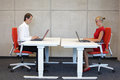 Business Man And Woman Working In Correct Sitting Posture With Laptops Sitting On Chairs Royalty Free Stock Image - 46930316