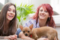 Couple Of Young Women Playing With A Small Dog Stock Image - 46937191