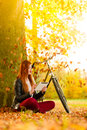 Woman In Autumn Park Using Tablet Computer Reading Stock Photography - 47184952