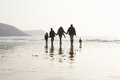 Rear View Of Family Walking Along Winter Beach With Dog Stock Photography - 47230312