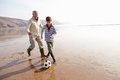Grandfather And Grandson Playing Football On Winter Beach Stock Images - 47231584