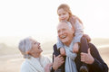 Grandparents And Granddaughter Walking On Winter Beach Royalty Free Stock Photography - 47231677