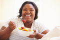 Overweight Woman Sitting On Sofa Eating Bowl Of Fresh Fruit Stock Images - 47235084