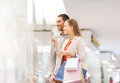 Happy Young Couple With Shopping Bags In Mall Stock Images - 47255714