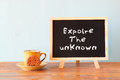 Blackboard With The Phrase Explore The Unknown Next To Cup Of Coffee And Cookie Royalty Free Stock Image - 47363686